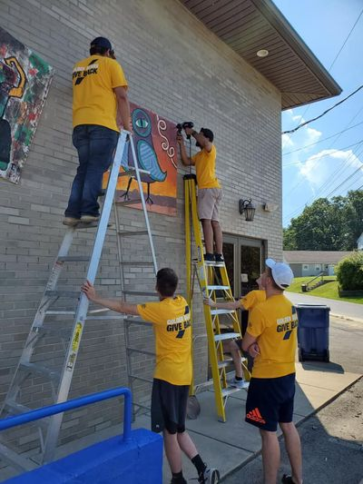 Student volunteers climb a ladder to paint during a service project.