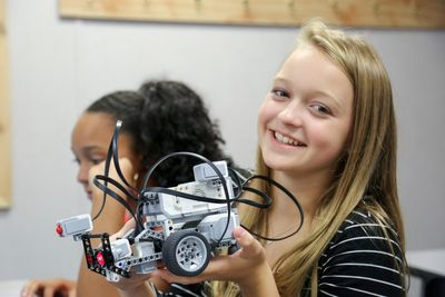 A student in the GIRLS program showcases her LEGO robot,