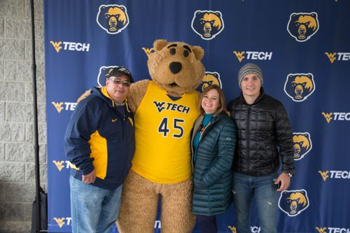 A family poses with Monty at Family Weekend