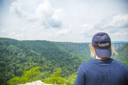 Female student looking from long point to New River Gorge Bridge