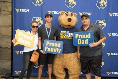 A family poses in front of a WVU Tech backdrop with Tech mascot Monty.