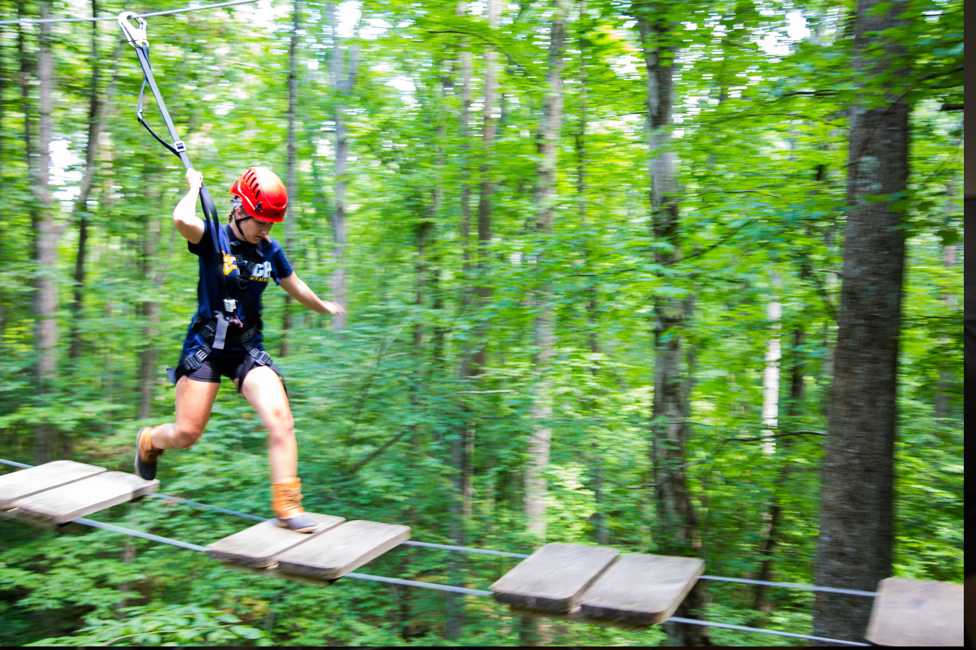 Woman moving across an open bridge on high ropes course