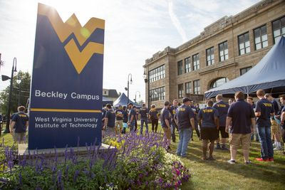 A large group of people mingle in front of Carter Hall with the WVU Beckley Campus sign in the foreground.
