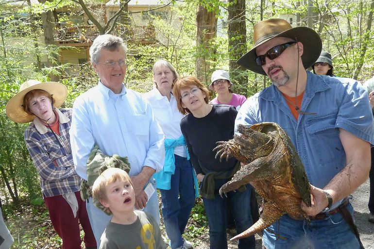Jim Anderson showing a snapping turtle to a crowd of people