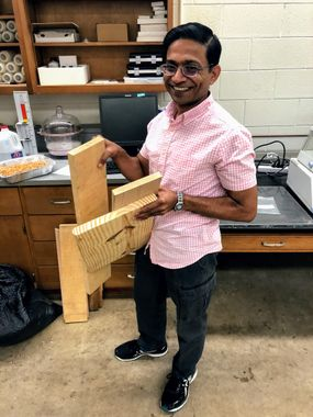 Kaushlendra Singh stands in his lab holding the three types of wood he is using for this research project: birch, red oak and longleaf pine.