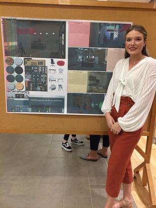 Interior Design student Kasey Helmick stands beside her award winning display, True Colors.