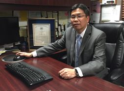 Image of Dr. Wang sitting at computer at his desk