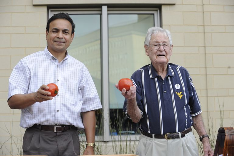 Mahfuz Rahman and Mannon Gallegly hold the new tomato varieties