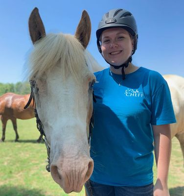 Victoria Chisler wearing a CHEFF shirt stands with a horse