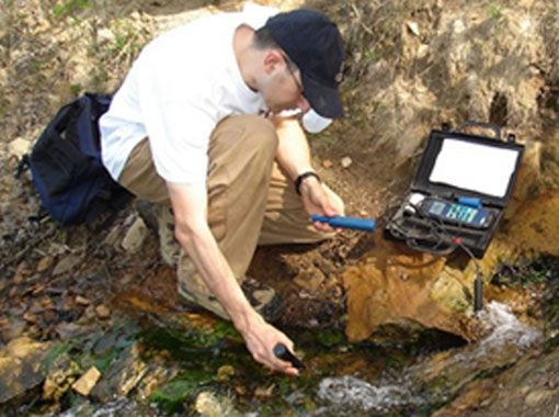 image of student testing water in stream
