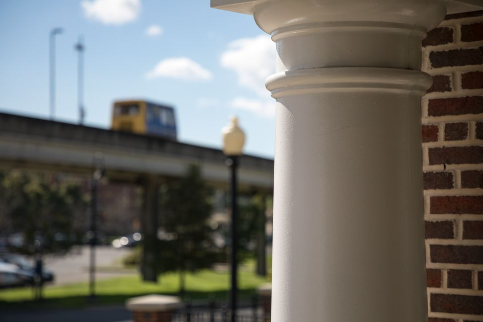 One of the Erickson Alumni Center Pillars with a PRT Car in the background