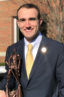 Tyler Brewster, Vice President standing in front of the Erickson Alumni Center holding a statue of the Mountaineer in his right hand