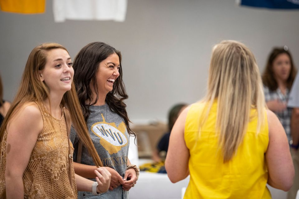 Three girls smiling and talking at a chapter event