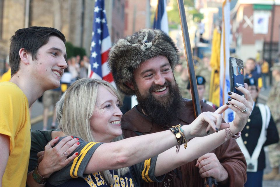 the WVU Mountaineer taking a selfie with fans