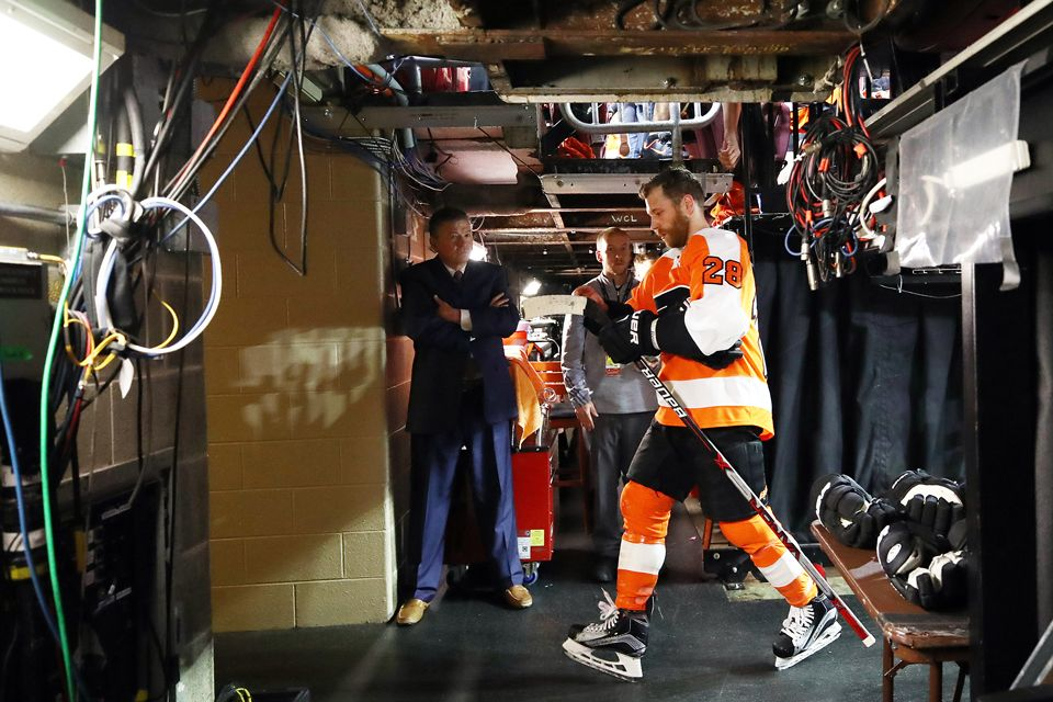 Zack Hill standing in the lockerroom watching a Philadelphia Flyers player walk out into the arena.