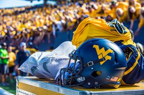 WVU Football Uniform sitting on a gold chest in Milan Puskar Stadium