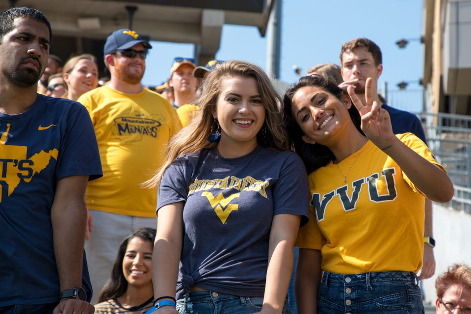WVU Football fans cheering in the stands.