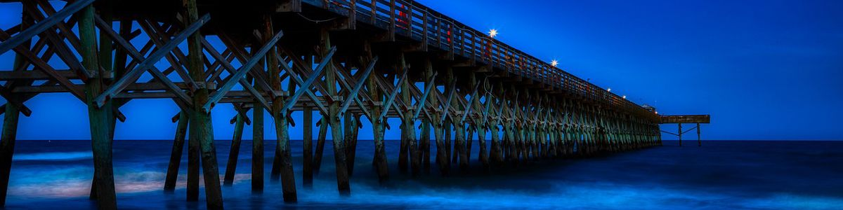 Pier at night with waves crashing.