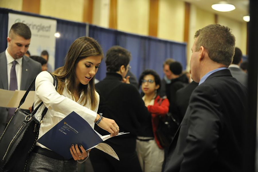 Student at a college career fair speaking with a recruiter