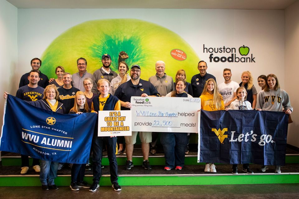The WVU Alumni Lone Star Chapter posing for a picture at the Houston Food Bank