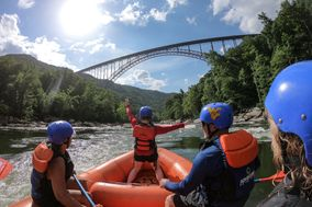 Rafters riding on the Gorge with a view of the New River Gorge bridge