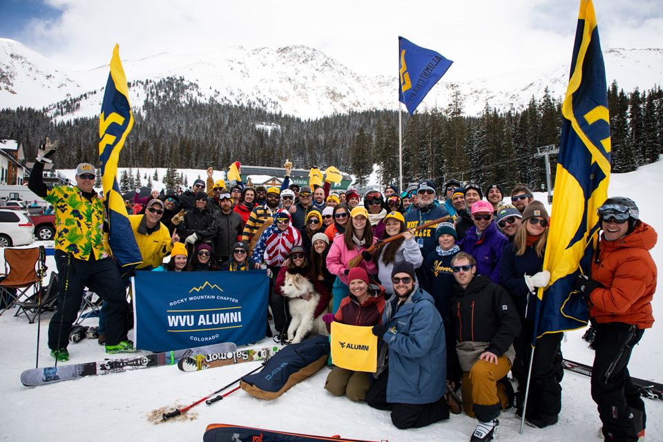 The WVU Alumni Rocky Mountain Chapter posing in front of snowy mountains