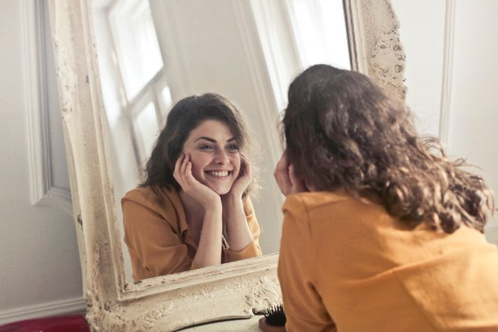 Young woman smiling at herself in the mirror