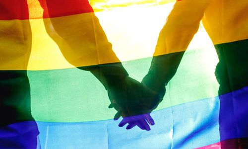 Two people holding hands in unity with backdrop of rainbow flag.