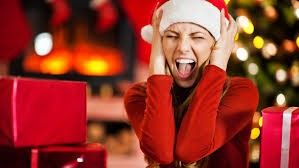 Screaming woman wearing a Santa hat in front of a Christmas tree