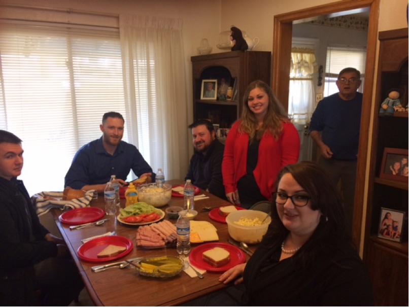 Veterans Advocacy Clinic Students (from left) James Dorsey, Alex Jonese, C.J. Reid, Kirsten Lilly and Rachel Roush, pose during a lunch graciously provided by United States Marine Corps Veteran Joe Gero (in doorway), of Madison, during the students' visit to VFW Post 5578.