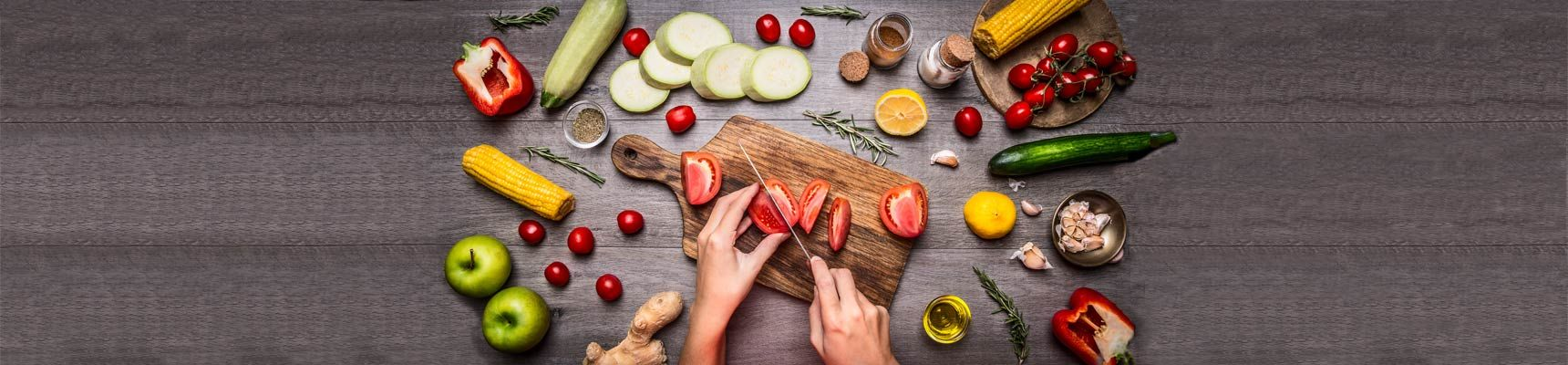 image of hands cutting up fruit and vegetables on cutting board