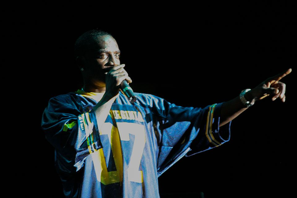 Akon wearing a WVU football jersey on stage at the Coliseum
