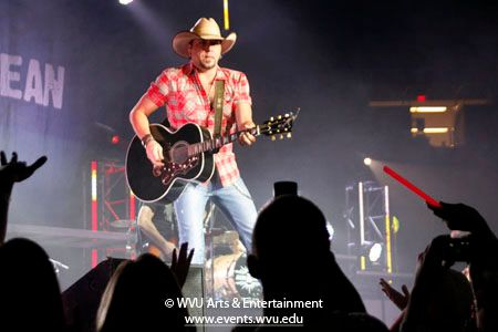 Close up photo of Jason Aldean playing guitar on the Coliseum stage