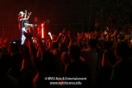 Photo of Jason Aldean on stage and clapping in unison with the crowd at the WVU Coliseum