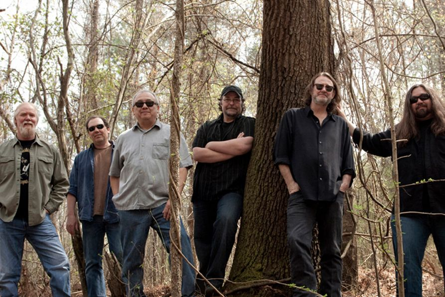 Members of Widespread Panic in a publicity photo set in the woods.