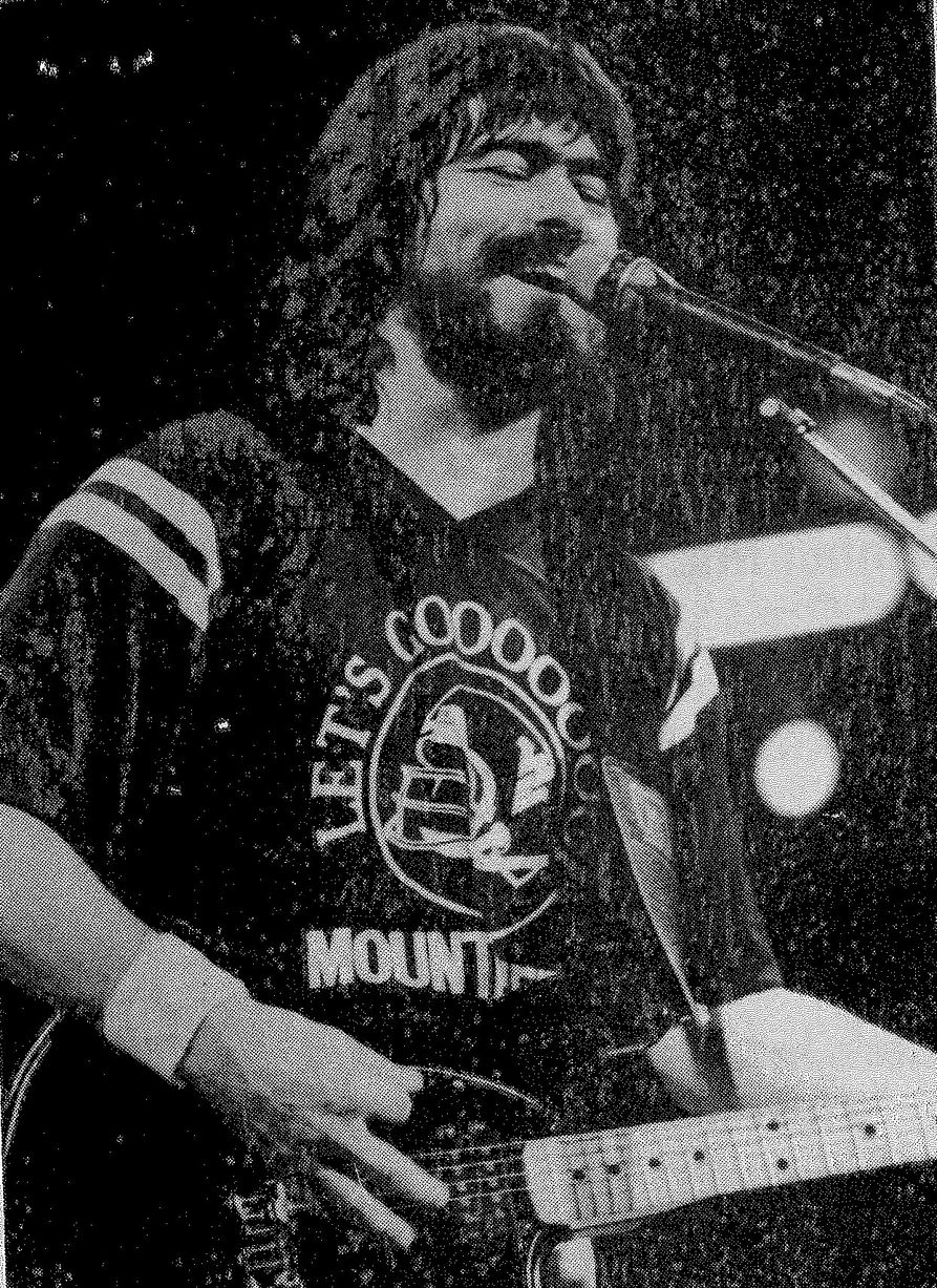 Black and white photo of Randy Owen performing on stage at the Coliseum while wearing a WVU t-shirt.
