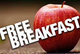 "Text ""free breakfast"" on a brown background that includes a red apple."
