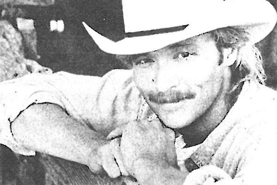 Photo of Alan Jackson with his guitar and his signature white cowboy hat.