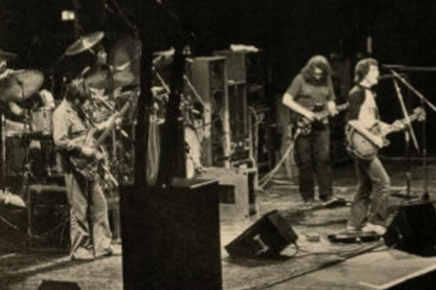 Black and white photo of the Grateful Dead performing at the Coliseum in 1983. Jerry Garcia and Bob Weir are both in the photo.