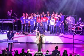 The Morgantown High School choir on stage with Foreigner at the WVU Creative Arts Center.