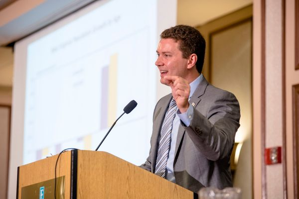 Man standing at a podium giving a lecture