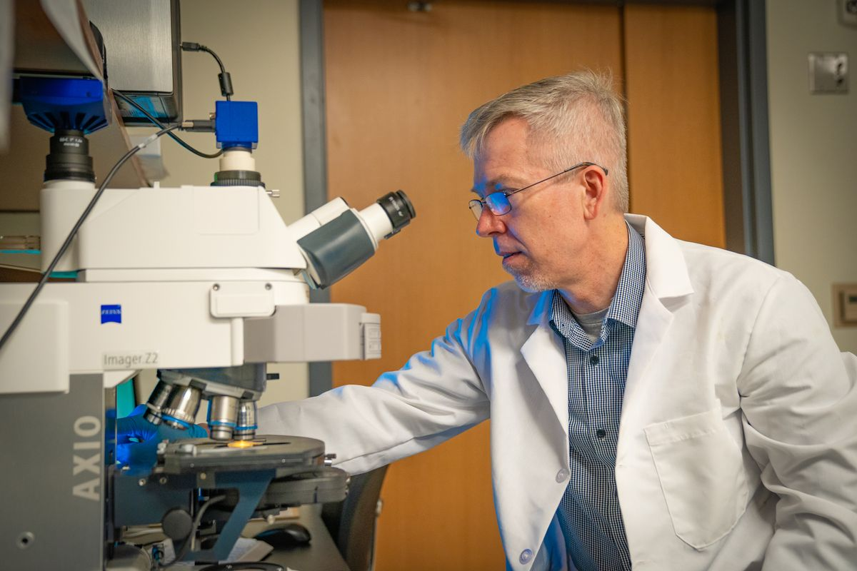 photo of man in white coat looking through microscope