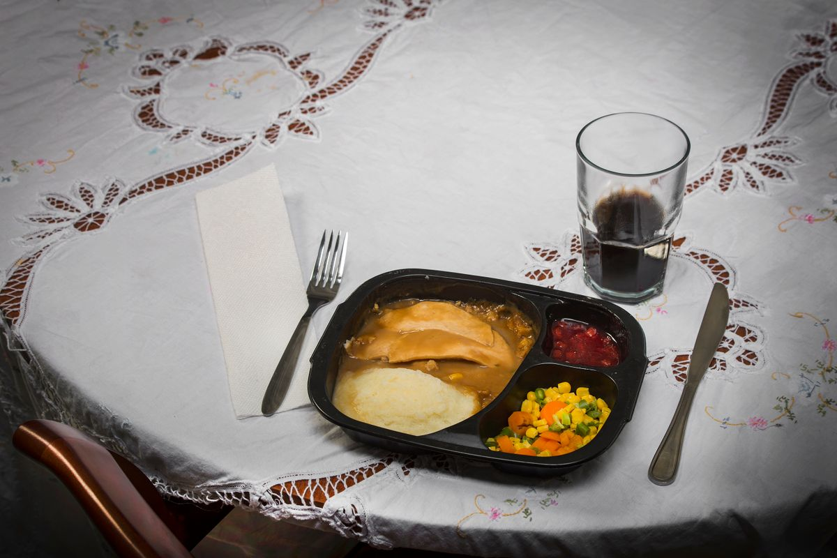 Plate of food on a table with silverware and a glass
