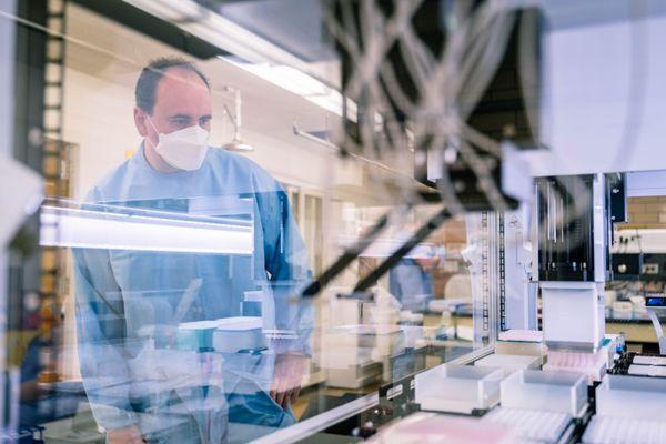 man in lab behind plexiglass barrier