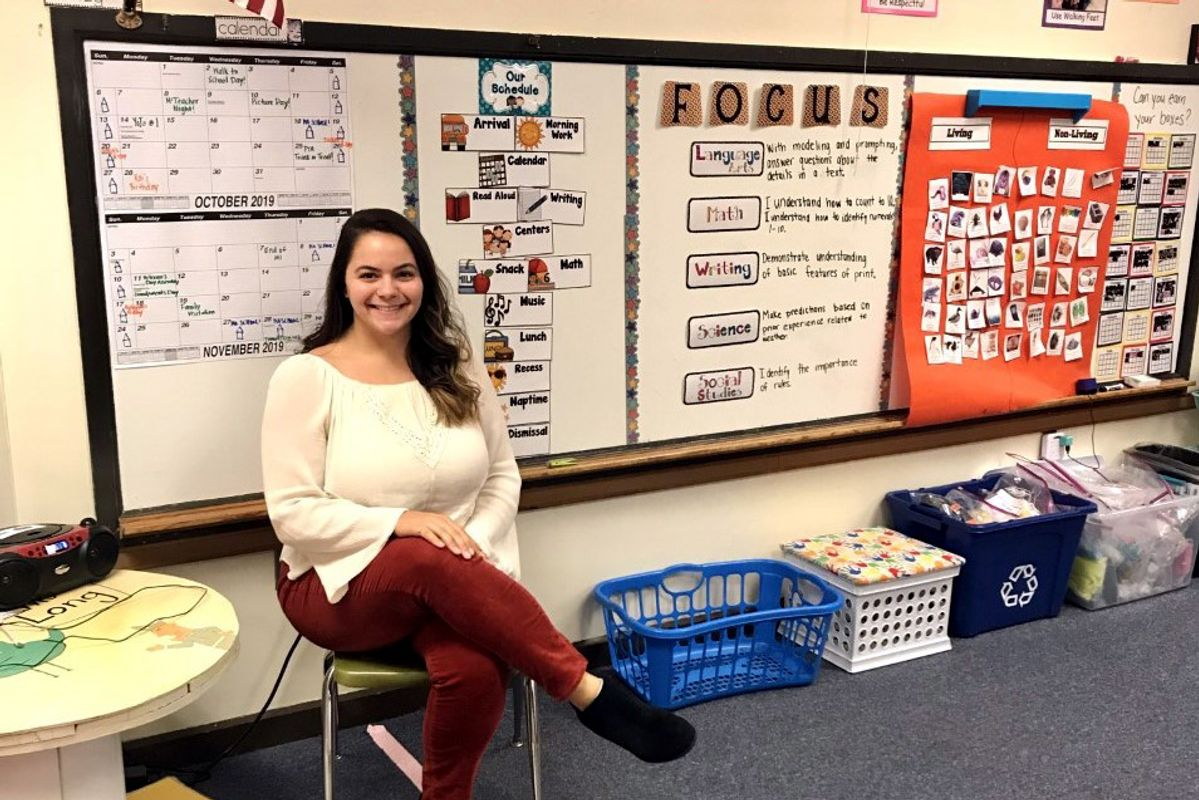 young woman sits by a white board filled with calendars and other educational material
