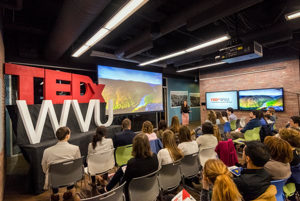 a woman talks to a group of people TEDX (in red) WVU (in white)
