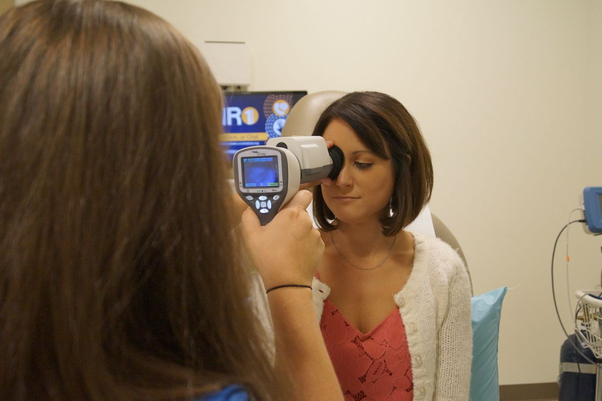 Doctor giving woman an eye exam with medical device