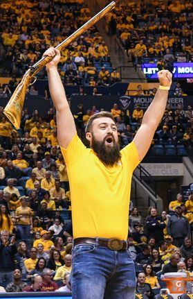 Trevor Kiess celebrates with raised arms Saturday, Feb. 24, as he's named the 2018-19 Mountaineer Mascot