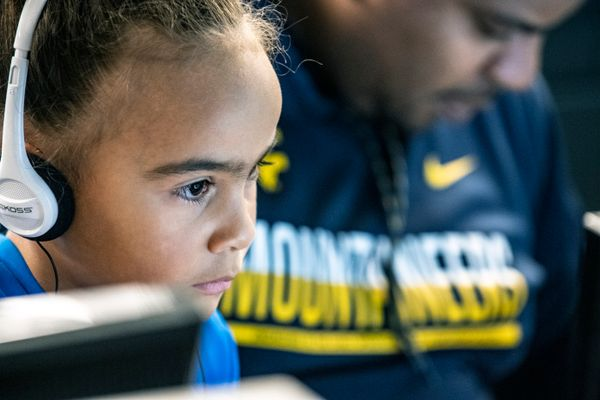 photo of child with headphones, adult in background