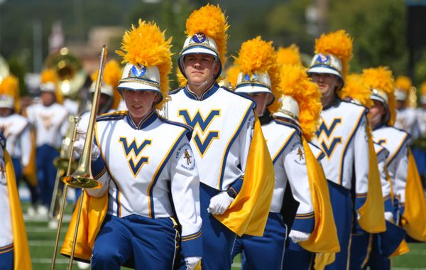 WV marching band marches in a line with their instruments in their right hands.